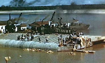 1940s: The Army Corps of Engineers uses an assembly barge to work on a revetment, along the Mississippi River, in the 1940s.