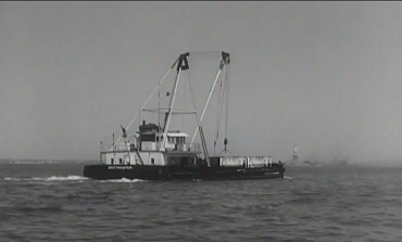 A ship, called drift master, sucks up floating debris from New York Harbor and the Army Corps of Engineers tests the portable DeLong Pier in the 1950s. (1950s)